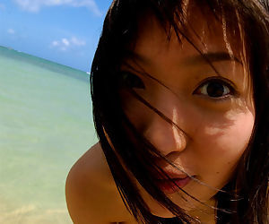 Stunning asian babe with big tits stripping off her bikini outdoor