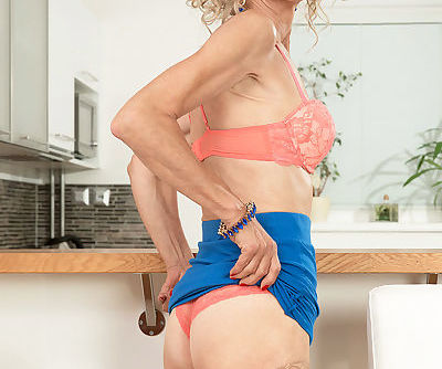 Old lady Beata slips off skirt and peach panties wearing tan colored stockings