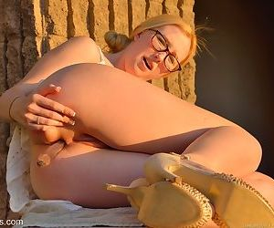 Sweet doll in glasses give a look at her hot pussy with dildo in the park