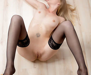 Young blonde Mila models in black stockings while displaying her tight pussy