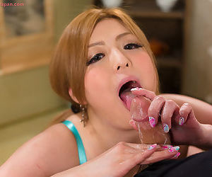 Japanese redhead licks jizz from her fingers after jerking off a cock