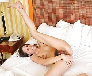 Hot babe Kitty Bush posing naked on the bed and toying her hairy cunt
