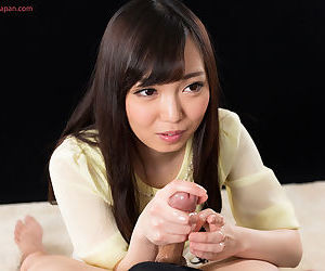 Japanese cutie flashes her bush before making eye contact while giving handjob