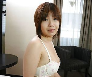 Frisky asian chick Naomi Nakane getting naked and exposing her unshaven twat