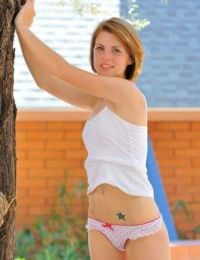 Redhead teen Aubrey shyly takes her time stripping off on the street
