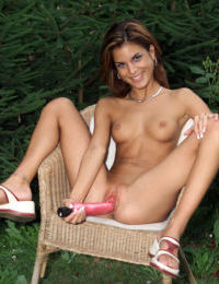 Slender Nella is caught without her bikini toying in the back yard