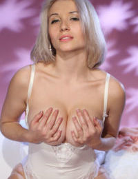 Young blonde Isabella D removes her white lingerie for nude posing on bed