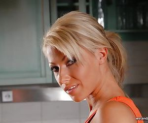 Blonde beauty Thea doffing shorts to finger her damp vagina on counter top