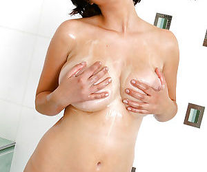 Young brunette babe Calista fondling her boobs in a foamy bath
