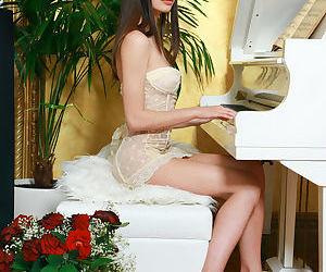 Slender young brunette Flora C shedding lingerie during glamour set