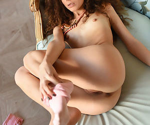 Curly young beauty Cualy with skinny body stripping on the couch
