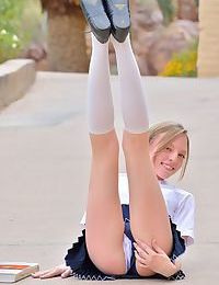 Tiny teen bares her little butt in the schoolyard and toys her bald beaver
