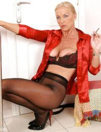Older Euro lady lets big boobs fall loose while enjoying cigarette