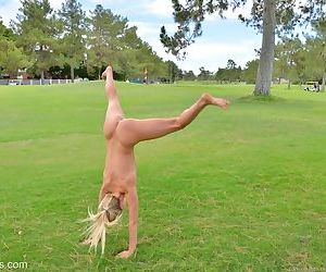 Sexy blonde girl shedding spandex pants and top to pose nude in public park