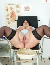 Buxom raiven-haired mature nurse in stockings revealing her jugs and twat
