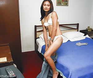 Seductive thai babe exposing her perky titties and shaved slit