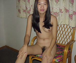 Naughty asian babe taking off her clothes and posing on the bed