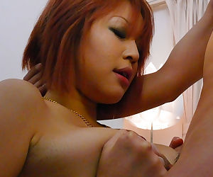 Redheaded Japanese chick taking cumshot on big tits after three way blowjob
