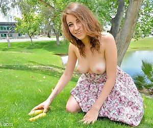 Young cutie in summer dress inserting vegetables into spread vagina