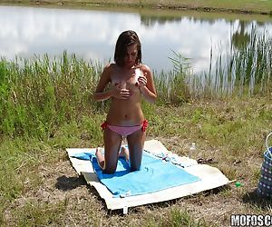 Amazing teen pet concerning closed heart of hearts Riley Reid posing nude open-air