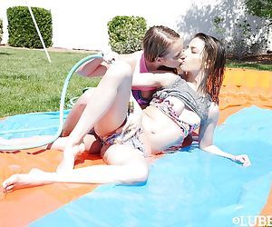Young lesbos Scarlett Sage and Kristen Scott eat pussy under sprinkler on lawn