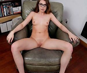 Young girl in glasses takes off her dress to pose nude for the first time