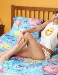 Sleeping teen girl awakes and takes off her clothes atop her bedspread