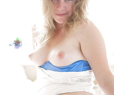 Pierced blonde beauty Ela removes both skirt and panties to bare ass