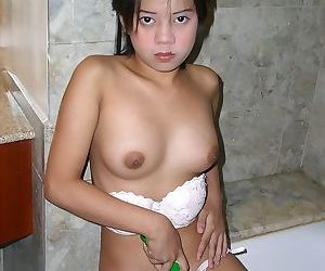 Young Asian girl toys her barely legal pussy in the bathtub