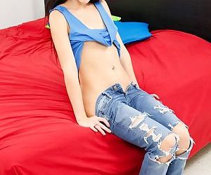 Small chested teenager Britt Shields posing solo in ripped denim jeans