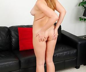 Hannah Heartley is masturbating naked on her black leather couch