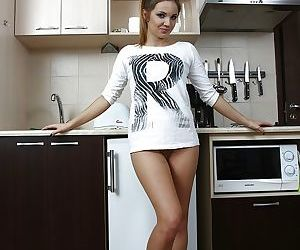 Amateur teen Linda Blink peeling off shorts and top to pose naked in kitchen