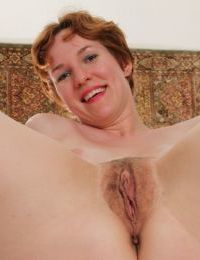 Sensual mature Clarissa is stroking her unshaved snatch and clit