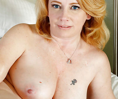 Chunky redheaded lady Brandie Sweet spreads pink pussy wide on bed