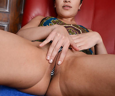 Middle-aged brunette Jade Rox showcases her bald cunt after getting naked