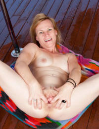 Mature woman Cody Hunter works an outdoor stripper pole while getting naked