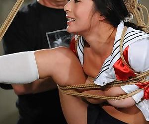 Asian female is suspended by ropes while enduring painful masturbation session