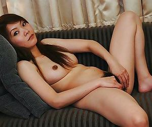 Asian chick undressing and exposing her racy flimsy twat in set right in the air