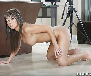 Hot Asian babe takes off her shorts to give a peek at her shaved cunt