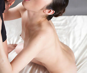 Naked young Asian girl kneels to give a blowjob and get a mouthful of cum