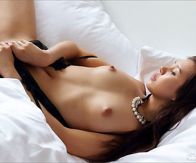 Erotic Asian girl slips out of her sexy black lingerie to roll nude on the bed