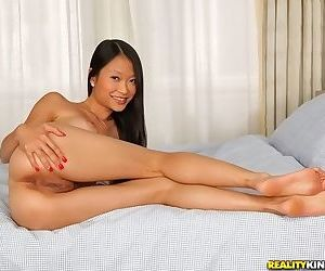 Slippy asian sweetie with round bosoms undressing and posing on the bed