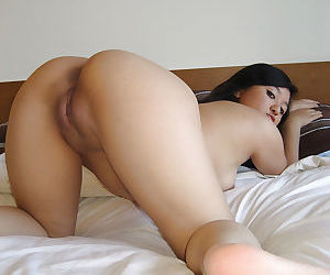 Frisky asian babe with small tits revealing her ample ass and inviting slit