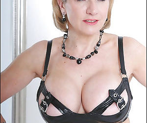 Stunning mature fetish lady with enhanced tits posing in latex outfit