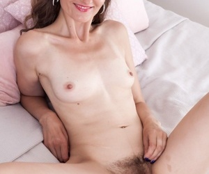 Mature slut Lulu removing her sexy lingerie to spread a hairy pussy
