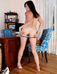 Older solo model Dixie Comet spreads her bare legs to show off her hairy muff