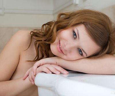 Beautiful erotic Demetra disrobes to pose her petite body nude in the bathroom