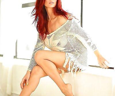 Redheaded Asian pornstar Tera Patrick revealing large juggs and tattoos