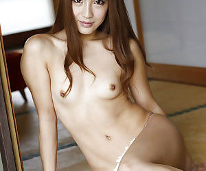 Cute Japanese babe Anna Anjo posing fully clothed on bed for close ups