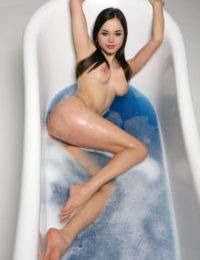 Beautiful Li Moon poses erotically with pussy lips spread in the bathtub